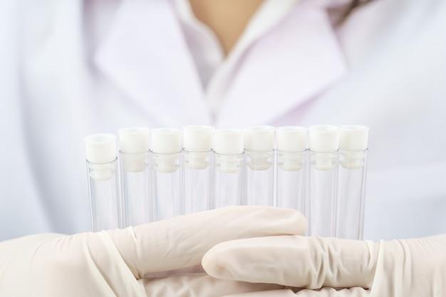 Technik naukowiec analizujący trzymanie probówki w laboratorium w celu przetestowania jej pod kątem covid, covid-19, analizy wirusa koronawirusa