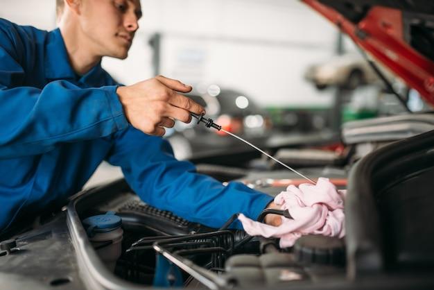 Technik płci męskiej sprawdza poziom oleju silnikowego samochodu za pomocą prętowego wskaźnika poziomu