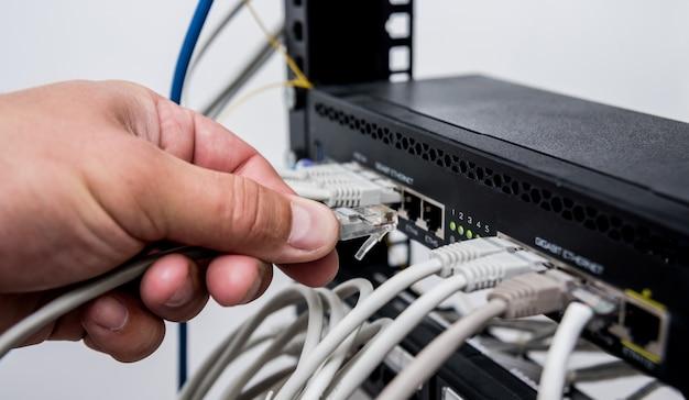 Technik podłączający kable sieciowe do przełączników. podłączanie kabli w szafie serwerowej.