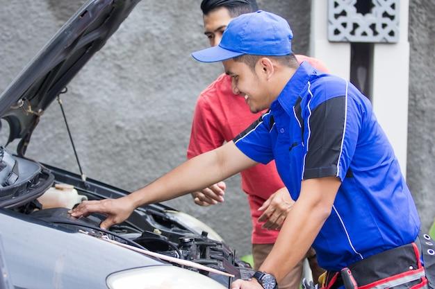 Technik pomaga klientowi naprawić swój samochód