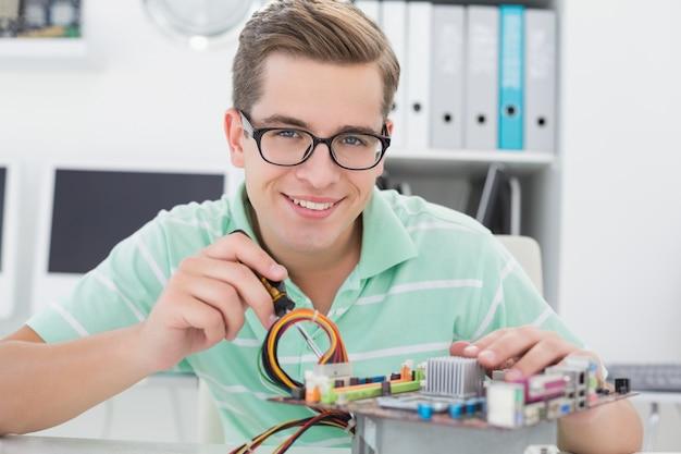 Technik pracuje na łamanej jednostce centralnej z śrubokrętem
