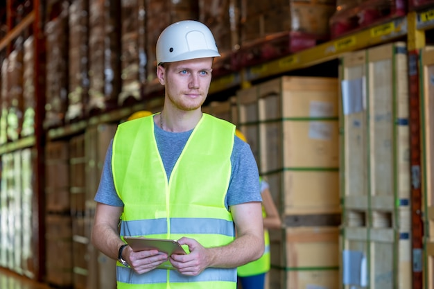Technik pracuje w handlu towarami w logistyce, pracownicy magazynu.