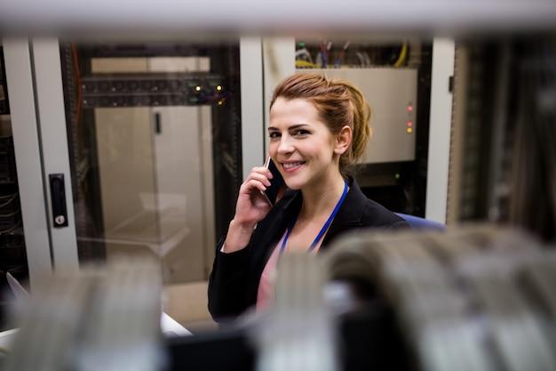 Technik rozmawia przez telefon komórkowy w serwerowni