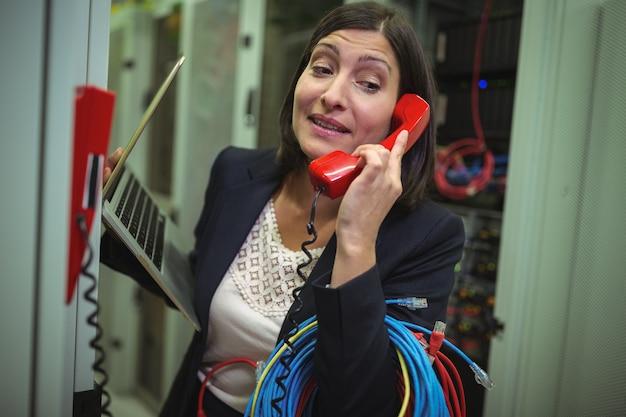 Technik rozmawia przez telefon podczas analizowania serwera