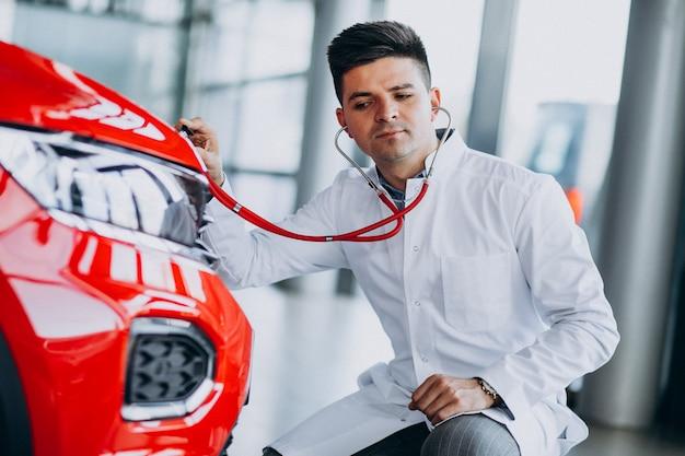 Technik samochodowy ze stetoskopem w salonie samochodowym