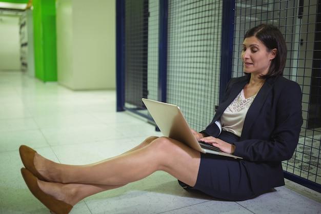 Technik siedzi na podłodze i korzysta z laptopa