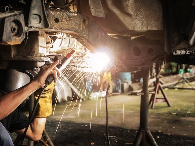 Technik spawa stal montażową pod samochodem w fabryce samochodowej.