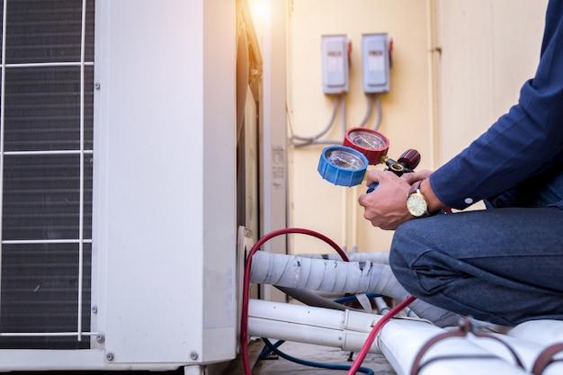 Technik sprawdza klimatyzator, mierzy urządzenia napełniające klimatyzatory.
