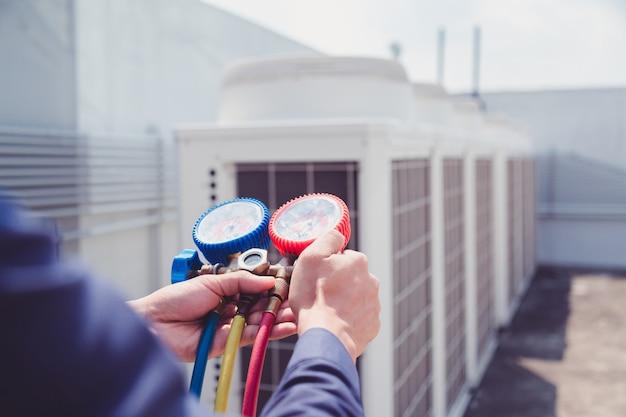 Technik sprawdza klimatyzator, sprzęt pomiarowy do napełniania klimatyzatorów.