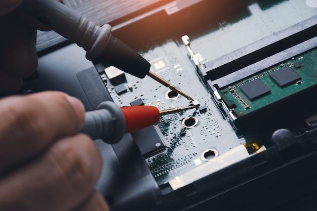 Technik sprawdzający płytkę drukowaną laptopa za pomocą multimetru