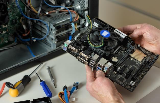 Technik trzyma płytę główną w obudowie komputera stacjonarnego z bliska