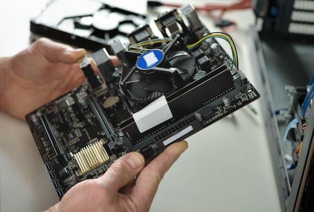 Technik trzyma płytę główną w obudowie typu desktop.