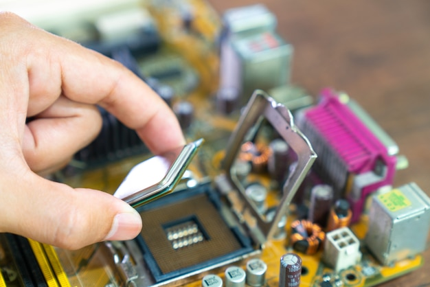 Technik umieszcza procesor na gnieździe płyty głównej komputera.