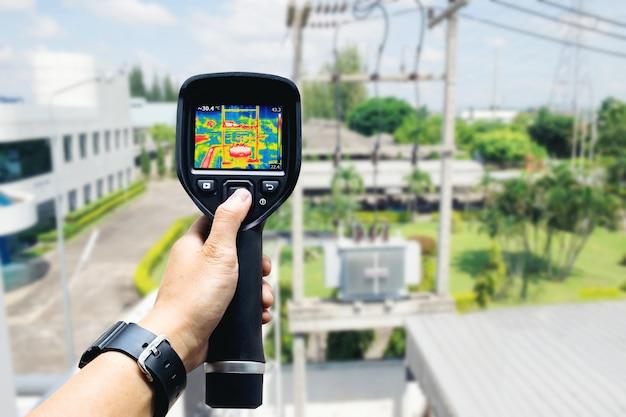 Technik używa kamery termowizyjnej do sprawdzania temperatury w fabryce