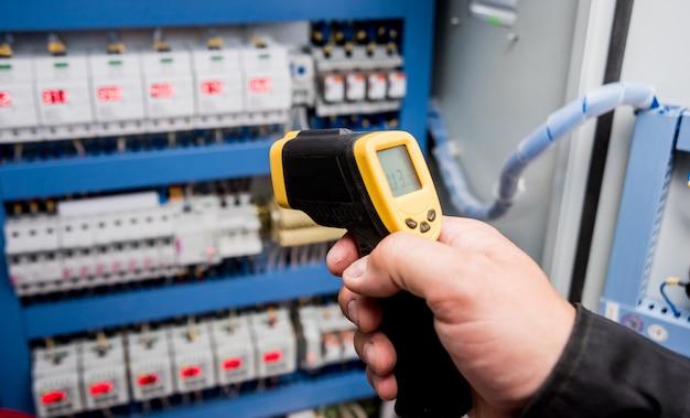 Technik używa kamery termowizyjnej na podczerwień do sprawdzania temperatury w skrzynce bezpieczników