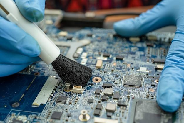 Technik używa pędzla i dmuchawy do czyszczenia kurzu w komputerze z płytką drukowaną