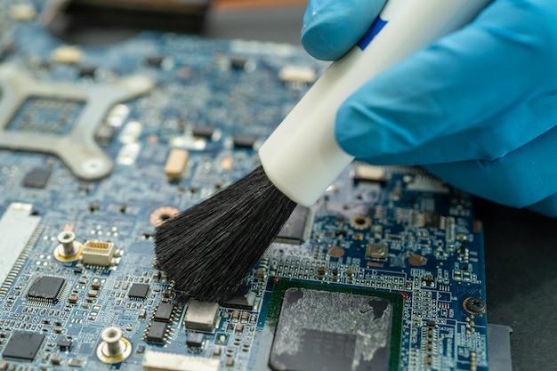 Technik używa pędzla i kulki dmuchawy do czyszczenia kurzu w komputerze z płytką drukowaną. naprawa technologii modernizacji i konserwacji.