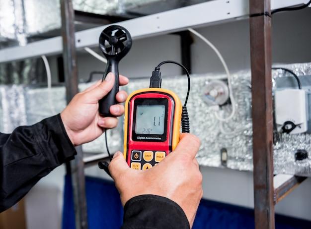 Technik używa ręcznego anemometru do pomiaru przepływu powietrza, prędkości i ciśnienia wiatru.