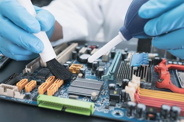Technik używa szczotki i dmuchawy powietrza do usuwania kurzu z komputera pokładowego.