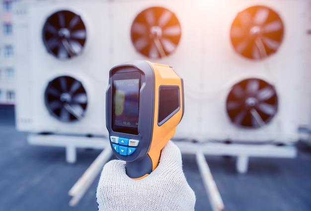 Technik używa termometru termowizyjnego na podczerwień do sprawdzania wymiennika ciepła agregatu skraplającego