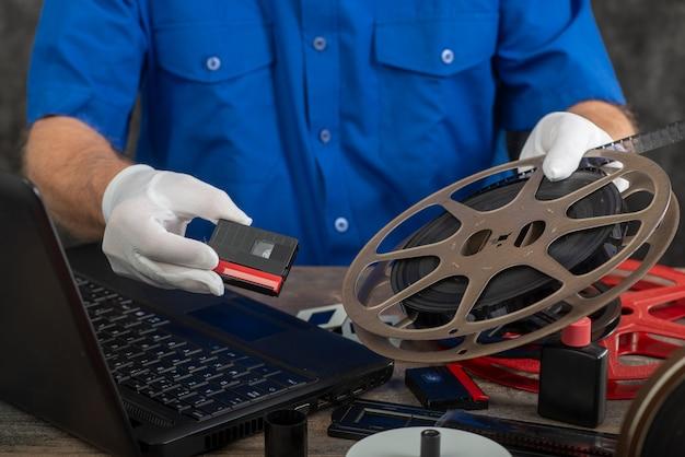 Technik w białych rękawiczkach digitalizujący stary film 16 mm i dv