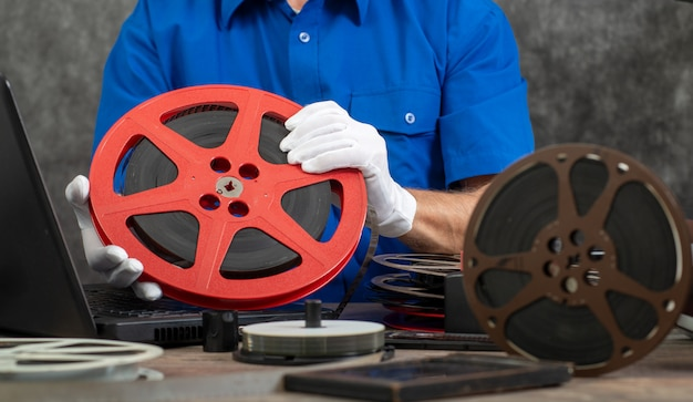 Technik w białych rękawiczkach digitalizujących stary film 16 mm