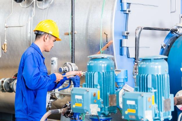 Technik w fabryce przy konserwacji maszyny