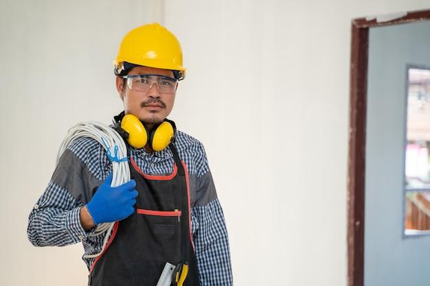 Technik w kasku trzymając kabel elektryczny z narzędziami pracującymi na budowie.