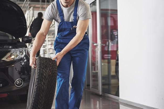 Technik w niebieskim ubraniu roboczym, trzymający klucz i oponę, pokazujący kciuk do góry.