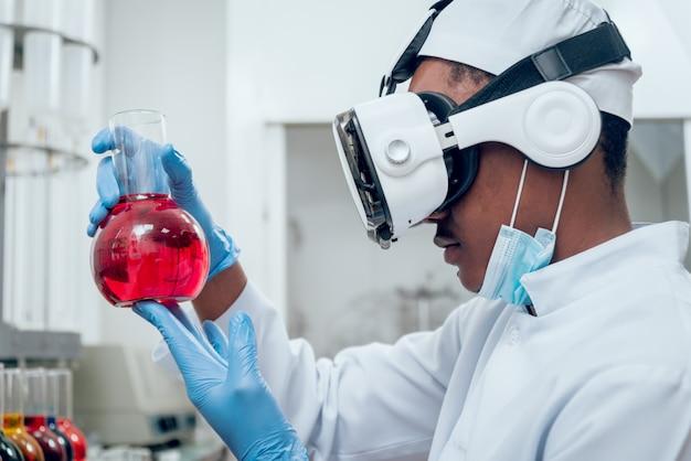 Technik w okularach rzeczywistości wirtualnej bada lek w laboratorium.