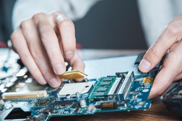 Technik wkłada procesor do gniazda na płycie głównej komputera