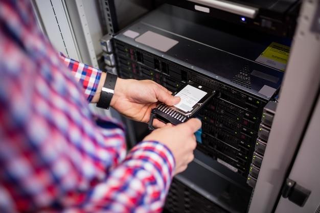 Technik wkładający dysk twardy do serwera typu blade