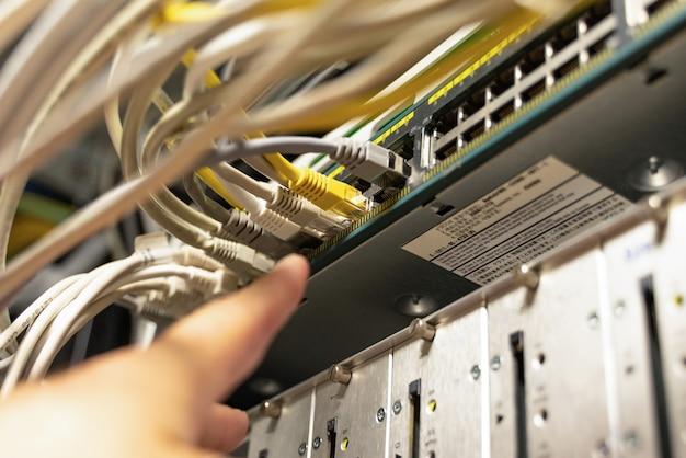 Technik wskazujący na kable w pomieszczeniu z kablami