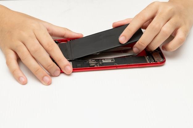 Technik wymienia baterię w telefonie komórkowym lub smartfonie.