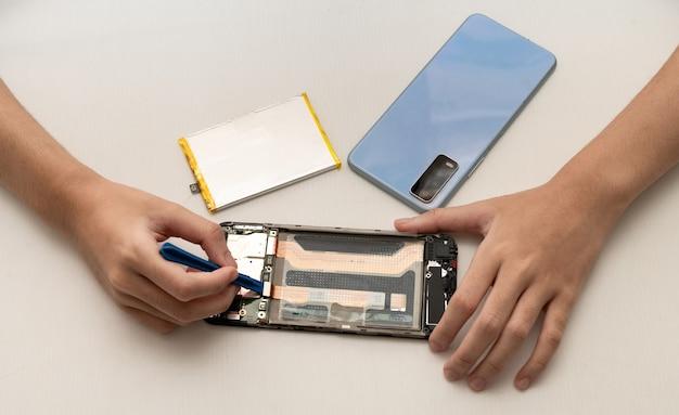 Technik wymienia baterię w telefonie komórkowym lub smartfonie