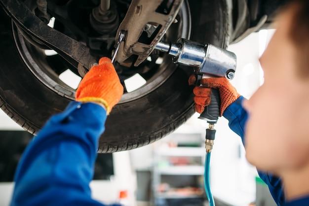 Technik z kluczem do naprawy zawieszenia samochodu