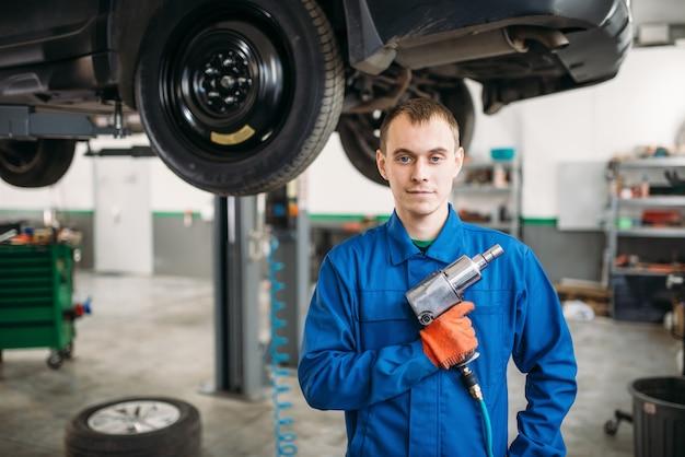 Technik z kluczem pneumatycznym, samochód na podnośniku.