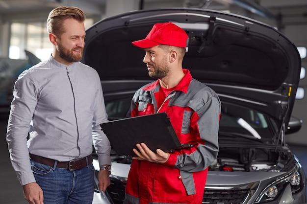 Technik z laptopem rozmawia z klientem oprócz samochodu