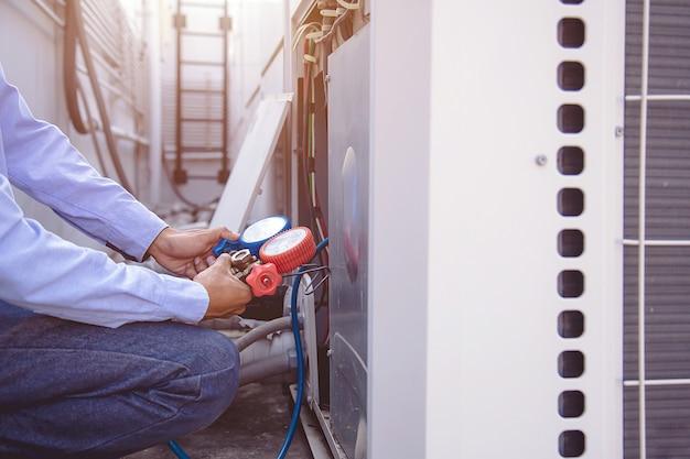 Technik za pomocą miernika kolektora mierzy urządzenia do napełniania przemysłowych klimatyzatorów fabrycznych.