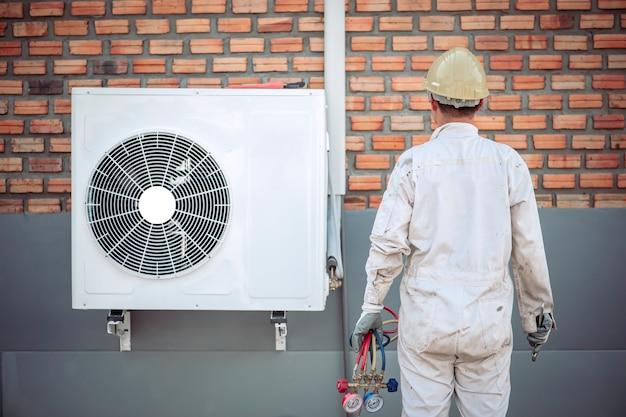 Technik zajmujący się klimatyzacją demontuje klimatyzator do przeglądu.