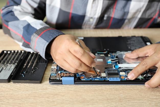 Technika mężczyzna używa śrubokrętu naprawiać lub ulepszać laptop
