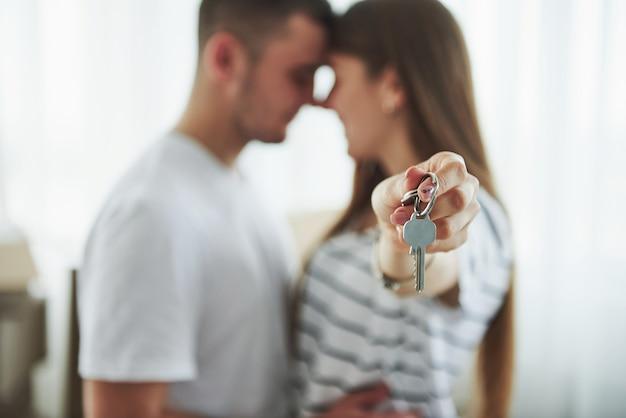 Technika ostrości obrazu. klucze do domu. wesoła młoda para w swoim nowym mieszkaniu. koncepcja ruchu.