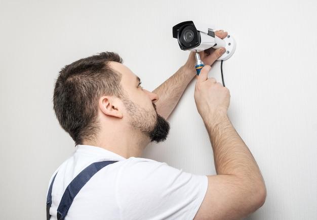 Technika pracownik instaluje kamera do nadzoru wideo
