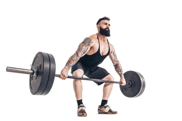 Technika wykonywania ćwiczenia martwego ciągu ze sztangą umięśnionego, wytatuowanego, brodatego sportowca