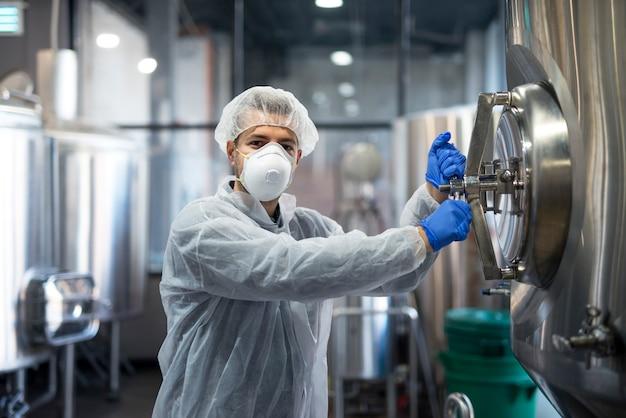 Technolog pracownik przemysłowy otwierający zbiornik technologiczny w fabrycznej linii produkcyjnej