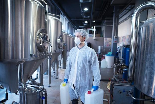 Technolog robotnik przemysłowy trzymający plastikowe kanistry o zmianie chemikaliów w maszynie do przetwarzania żywności