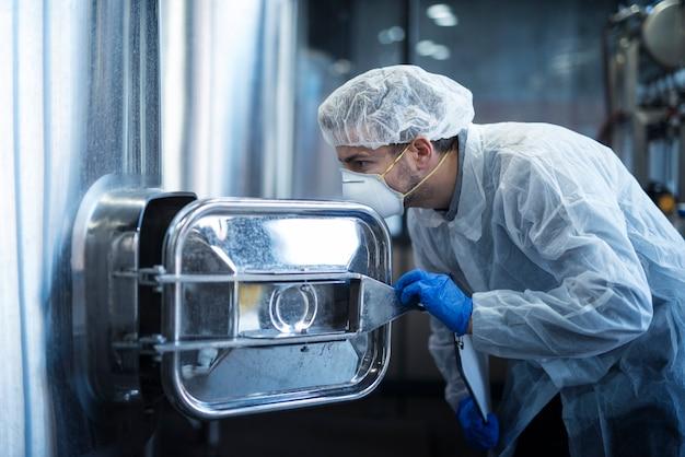 Technolog robotnik przemysłowy w kombinezonie niebezpiecznym obsługującym materiały agresywne w przemyśle chemicznym