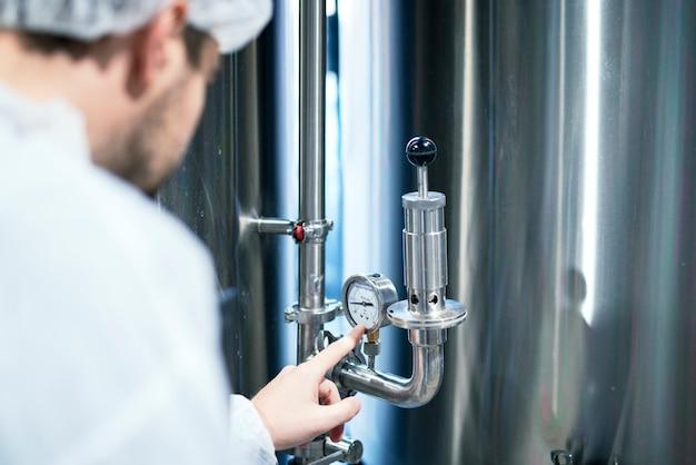 Technolog w białym kombinezonie ochronnym dokonujący pomiaru manometru na maszynie przemysłowej zamykającej zawór.