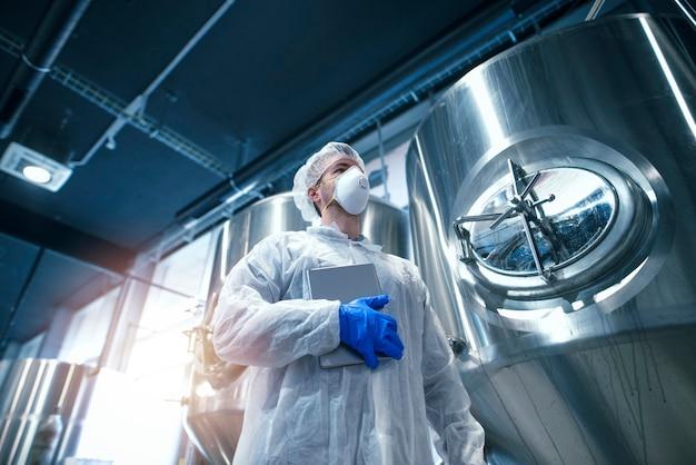 Technolog w białym kombinezonie ochronnym z siatką na włosy i maską ochronną pracujący w zakładzie produkcyjnym.