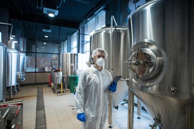 Technolog w białym mundurze ochronnym trzymający tabletkę i kontrolujący produkcję żywności w zakładzie przetwórczym